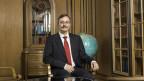 Rektor Michael Hengartner sitzt auf einem Stuhl in einem dunklen Holzbüro an der Universität Zürich.