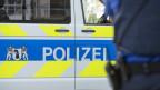 Ein Polizist der Kantonspolizei Basel-Stadt vor einem Polizeiauto.