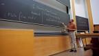 Ein Professor erklärt Formeln an einer grossen Wandtafel