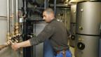 Ein Heizungsfachmann bei der Arbeit in einem Keller in einem Gebäude.