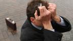 Ein Mann mit Zigarette in der Hand hält sich die Hände vors Gesicht.