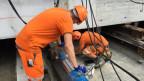 Orange gekleidete Arbeiter kontrollieren eine Hydraulikpresse