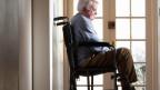Senior im Rollstuhl am Fenster