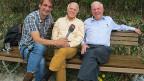 Thomy Scherrer auf einer Bank mit Walter Andreas Müller und Christoph Blocher.