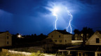 Ein Blitz schlägt nachts in einem Dorf ein.