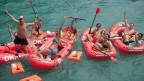 Junge Leute in roten Schlauchbooten auf dem Fluss.