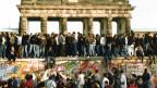 Auf der Mauer vor dem Brandenburger Tor wird der Mauerfall von Ost- und Westdeutschen gefeiert (Bild: Keystone)