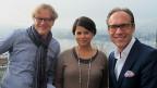 Ludwig Wicki und Sita Mazumder mit Christian Zeugin auf einem Balkon, dahinter Luzern und See im Nebel.