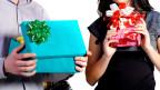 Zwei Leute mit Geschenk in der Hand.