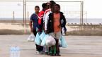 Wartende Gruppe von Flüchtlingen an einem Hafen