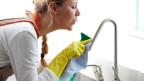 Frau putzt Wasserhahn.