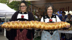 Zwei Frauen in Tracht halten einen riesigen Butterzopf.