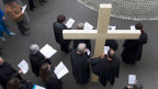 Leute mit Gesangsbüchern in der Hand und in der Mitte von ihnen ein Holzkreuz.