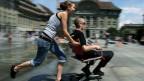 Junge Frau stösst jungen Mann im Bürostuhl über den Bundesplatz.