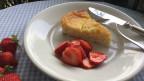 Ein Stück Ricotta-Törtchen auf einem weissen Teller mit Erdbeeren dekoriert.