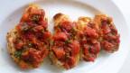 Vier Crostini mit Tomaten auf einem weissen Teller.