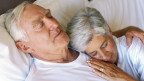 Älteres Paar liegt im Bett.
