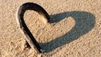 Holzast auf Sandstrand wirft einen Schatten und bildet ein Herz