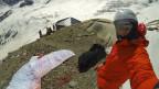 Mann mit Helm und Gleitschirm bei einer SAC-Hütte.
