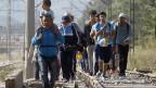 Flüchtlinge gehen auf Bahngeleisen.