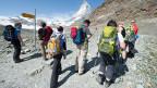 Wandergruppe steht auf einem Plateau vor dem Matterhorn.