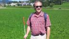 Martin Huwyler steht mit seinem weissen Blindenstock in der Hand am Wegrand auf dem offenen Feld zwischen Baar und Zug.