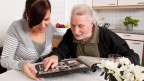 Eine junge Frau und ein älterer Mann schauen sich gemeinsam ein Fotoalbum an.