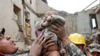 Helfer hält ein gerettetes Baby in die Luft.
