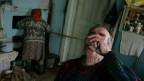 Mann trinkt Vodka und eine Frau heizt mit Holz ein.