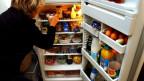 Eine Frau sucht etwas in einem vollen Kühlschrank, dessen Türe offen steht.