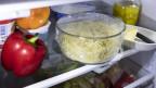 Eine Schüssel Teigwaren und andere Essensreste in einem Kühlschrank.