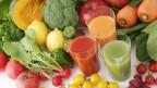 Gläser mit Saft drin stehen inmitten verschiedener Früchte- und Gemüsesorten.