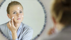 Junge Frau cremt ihr Gesicht ein vor dem Spiegel.