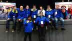 Eine Gruppe von Leuten in blauen Jacken posieren für ein Bild.