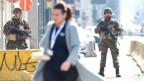 Eine Frau geht durch die Innenstadt von Brüssel, die von Soldaten bewacht wird.