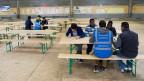 Asylbewerber sitzen in einer grossen Halle an einem Tisch.