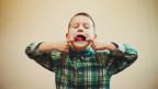 Ein Junge streckt die Zunge raus und macht eine Grimasse.