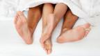 Weibliche und männliche Füsse im Bett.