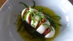 Eingeschnittener Mozzarella di Bufala. In den Einschnitten steckt eine konfierte Tomate.