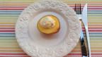 Auf Teller angerichteter warmer Pfirsich mit einem Klacks Vanilleglace