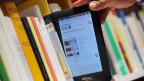 Jemand zieht einen E-Book-Reader aus einem Büchergestell.