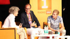 Die drei Gesprächsgäste sitzen in einer Runde auf der Bühne.