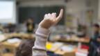 Ein Kind hält die Hand hoch im Schulunterricht.