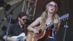 Margo Price auf der Bühne. Sie hat eine Sonnenbrille in Herzform auf der Nase.