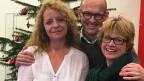 Katharina Albertin, Reto Waidacher und Daniela Lager posieren vor einem Weihnachtsbaum..