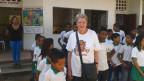 Silvia Haug steht vor einer Schule in Kolumbien. Die Schülerinnen und Schüler sind weiss grün uniformiert und stehen in Reihe und Glied.
