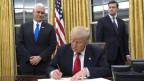 Donald Trump sitzt am Schreibtisch und unterschreibt ein Dokument.