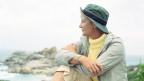 Frau mit Hut schaut in die Ferne.