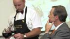 Ein Sommerlier schenkt an einer Meisterschaft dem Gast Wein ein.