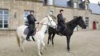 Mathias Häfeli mit seinem Partner Michael Linhoff vor ihrem Schloss. Mathias sitzt auf einem schwarzen Pferd, Michael auf einem Weissen.